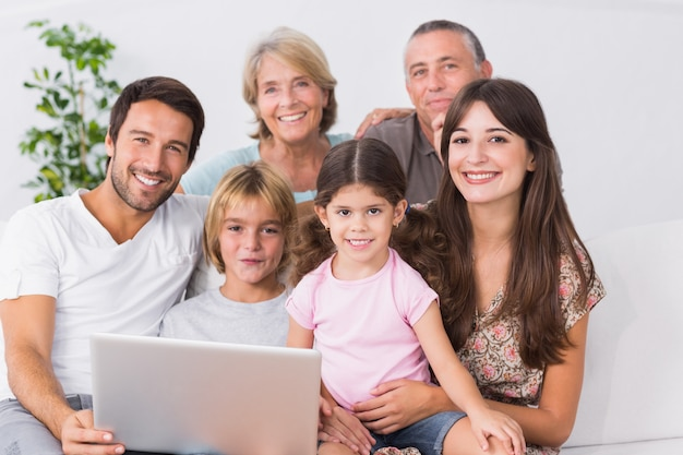 Happy family on couch using laptop Premium Photo
