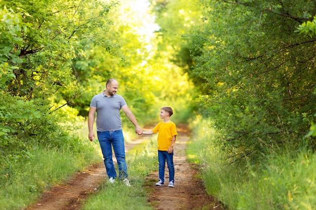 Счастливая семья: папа и сын гуляют, держась за руки летом Premium Фотографии