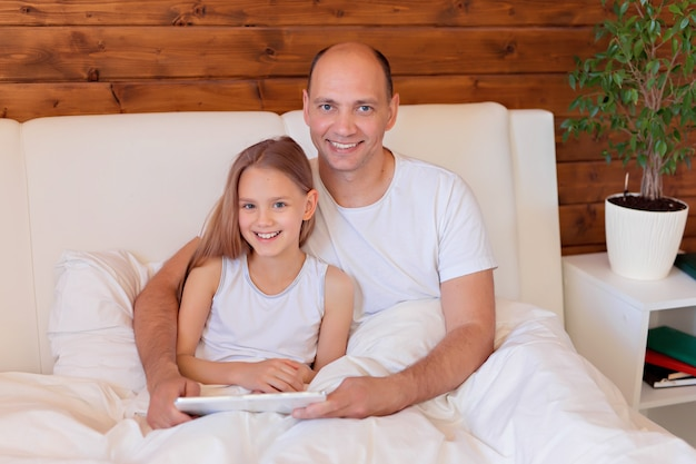 Happy family, dad and daughter talking on the tablet at home in bed. distance learning. Premium Photo