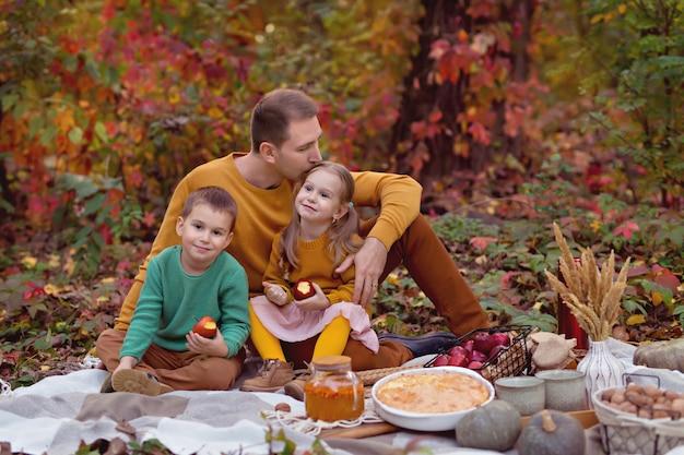 幸せな家族のお父さん、幼い息子、ケーキ、カボチャ、お茶と秋のピクニックの娘 Premium写真