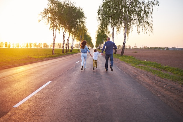 Happy family dad mom and son playing outdoors on the road near the field, Premium Photo
