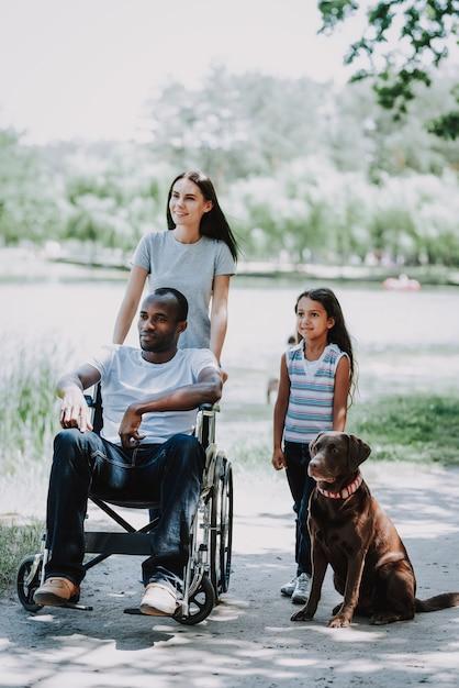 Happy family and dog outdoor paraplegic father Premium Photo