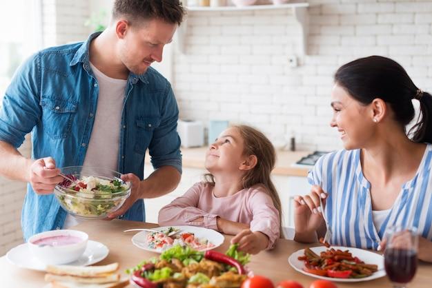 Счастливая семья ест вместе Premium Фотографии