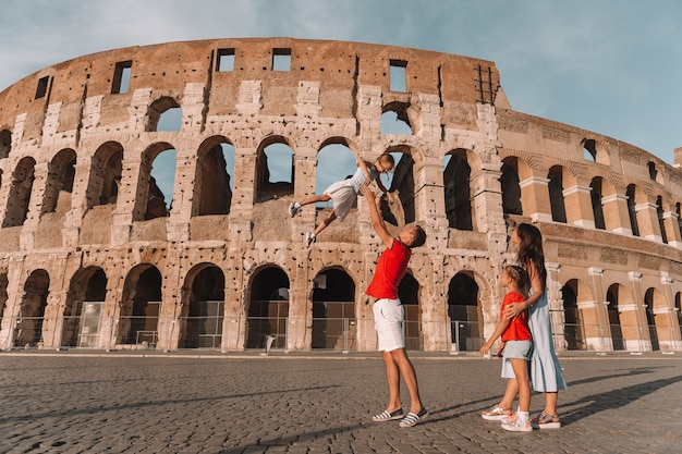 Happy family in europe. parents and kids in rome over coliseum Premium Photo