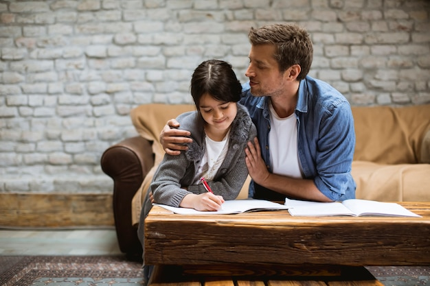 Happy family father and daughter doing homework at home Premium Photo