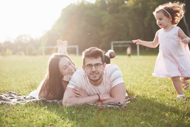 Happy family, father of mother and daughter of baby in the nature at sunset Free Photo