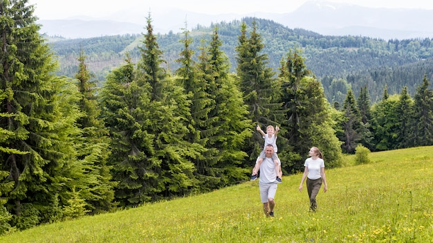 Happy family: father with son on shoulders and mother walking on a green field against the coniferous forest and mountains. Premium Photo