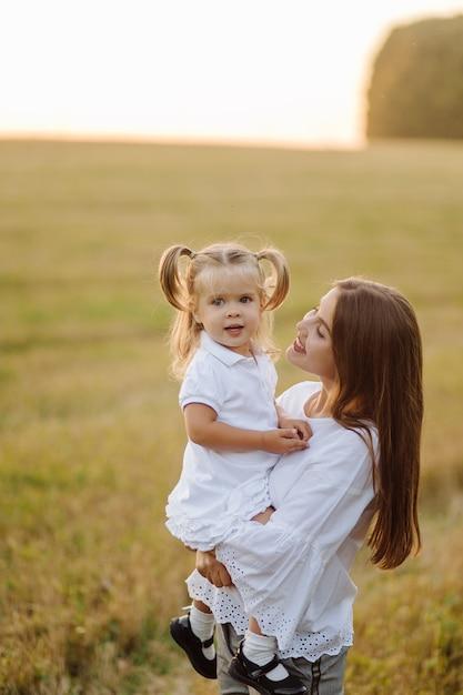 Famiglia felice in un campo in autunno. madre, padre e bambino giocano nella natura sotto i raggi del tramonto Foto Gratuite