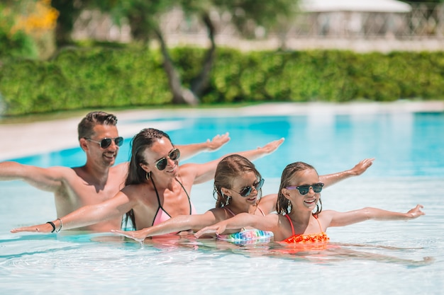 Happy family of four in outdoors swimming pool Premium Photo
