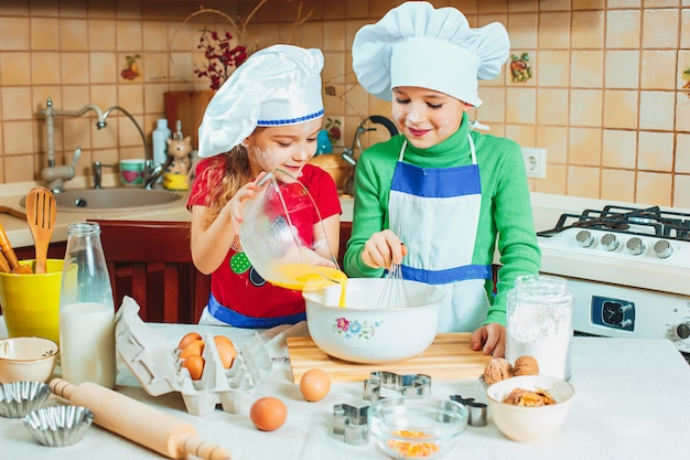 Happy family funny kids are preparing the dough, bake cookies in the kitchen Free Photo