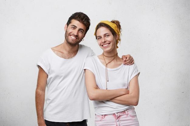 幸せな家族:ハンサムなひげを生やした男性が手を組んで立っている愛で妻を抱きしめ、笑顔で夫の世話を感じて幸せです。白い壁に孤立したハグの若者 無料写真
