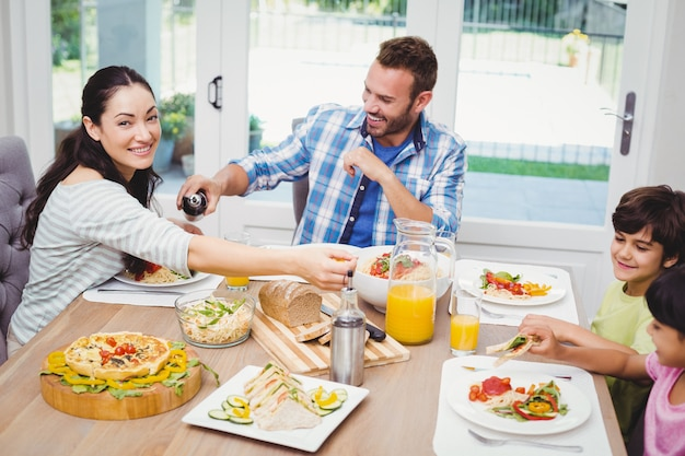 Happy family having food while sitting at dining table Premium Photo