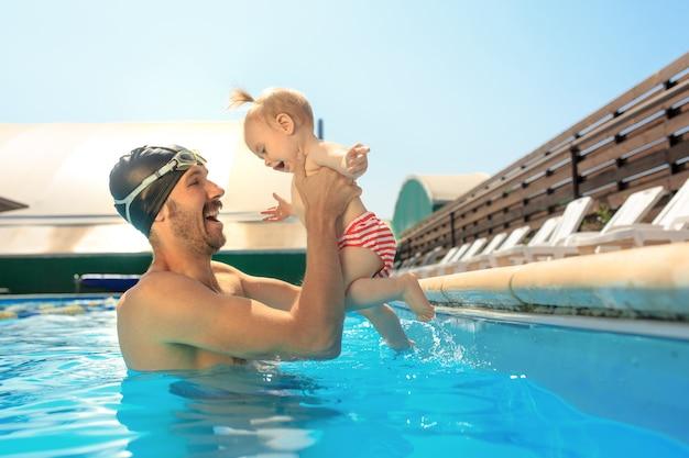 Famiglia felice che si diverte a bordo piscina Foto Gratuite