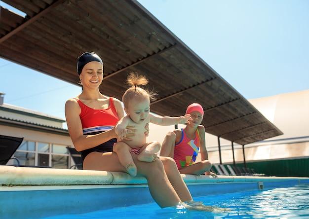 スイミングプールで楽しんで幸せな家族。 無料写真