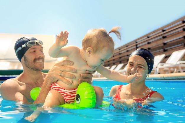Счастливая семья веселится у бассейна Бесплатные Фотографии