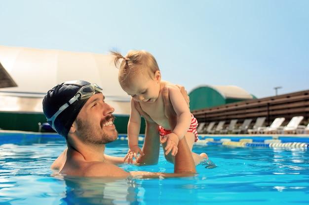 スイミングプールで楽しんで幸せな家族 無料写真