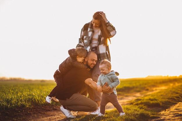夕日のフィールドで楽しんで幸せな家族 無料写真