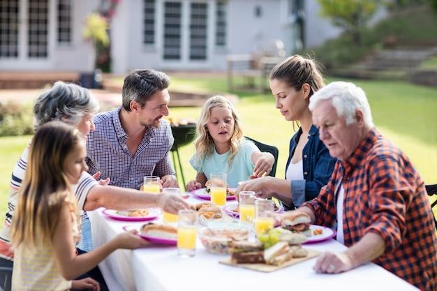 庭で昼食を食べて幸せな家族 Premium写真