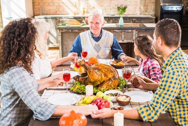 Happy family holding hands at table with food Free Photo