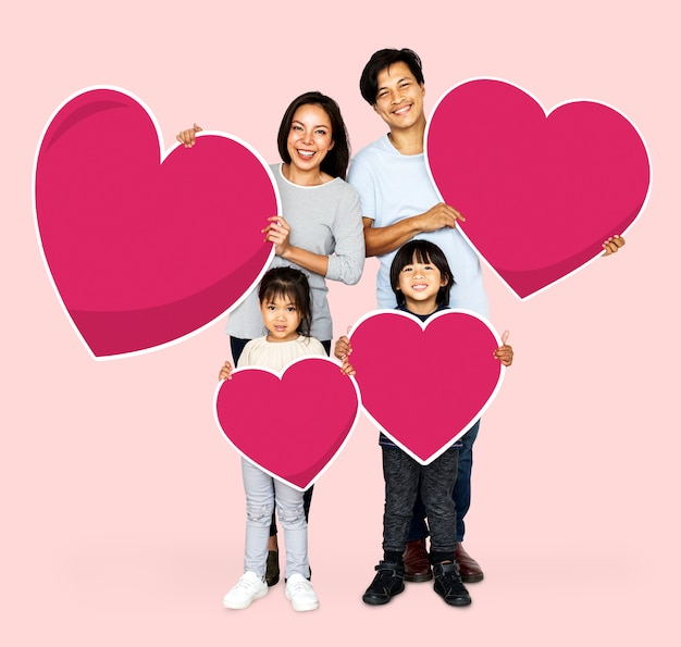 Happy family holding heart shapes Free Photo