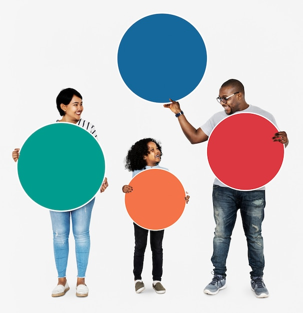 Happy family holding round colorful boards Free Photo
