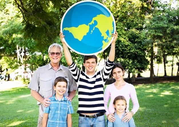 Happy family holding up the globe Premium Photo
