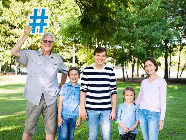 Happy family holding up hashtags Premium Photo
