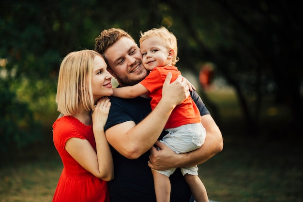 Happy family hugging their child Free Photo