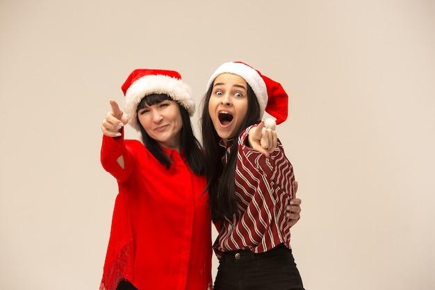 クリスマスセーターポーズで幸せな家族。愛の抱擁、休日の人々を楽しんでいます。スタジオで灰色の背景にママと娘 無料写真