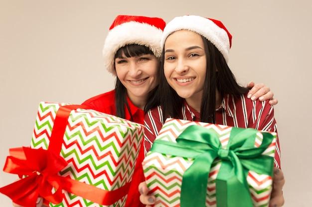 크리스마스 스웨터 선물 포즈에 행복 한 가족입니다. 사랑을 즐기는 포옹, 휴일 사람들. 엄마와 스튜디오에서 회색 배경에 Doughter 무료 사진