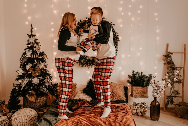 Счастливая семья в пижаме с детьми и родителями играет с ребенком, прыгающим на кровати в спальне. новогодняя семейная одежда смотрится нарядами. подарки на день святого валентина Premium Фотографии