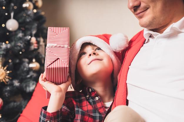 Счастливая семья в шляпе санта-клауса, отец и ребенок сын делают рождественский подарок дома Premium Фотографии