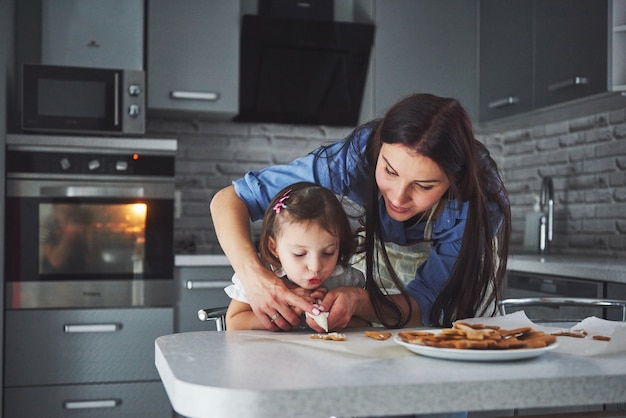 台所で幸せな家族。休日の食品のコンセプト。母と娘はクッキーを飾ります。自家製ペストリーを作るのに幸せな家族。自家製料理と小さなヘルパー 無料写真