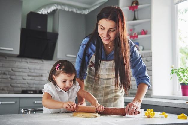 台所で幸せな家族。休日の食品のコンセプト。母と娘が生地を準備して、クッキーを焼きます。家でクッキーを作るのに幸せな家族。自家製料理と小さなヘルパー 無料写真