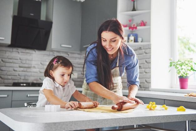 Счастливая семья на кухне. концепция праздника питания. мать и дочь готовят тесто, пекут печенье. счастливая семья в создании куки у себя дома. домашняя еда и маленький помощник Бесплатные Фотографии
