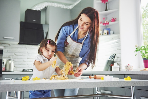 台所で幸せな家族。母と娘が生地を準備して、クッキーを焼きます。 無料写真