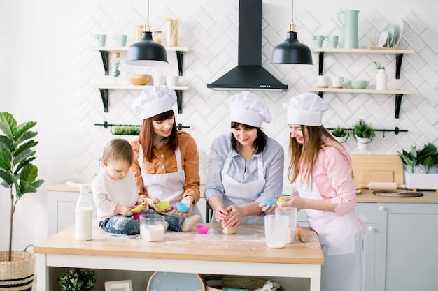 台所で幸せな家族。若い女性と彼女の妹、中年の女性、母の日のカップケーキを調理するかわいい娘、実生活のインテリアでカジュアルなライフスタイルの写真シリーズ Premium写真