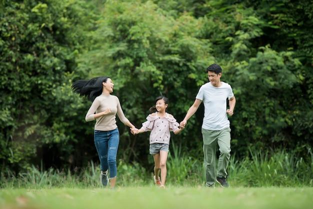행복한 가족이 재미 어머니, 아버지와 딸이 공원에서 실행 중입니다. 무료 사진