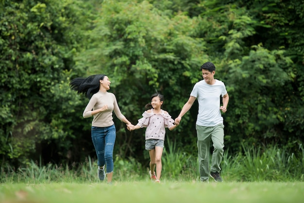 Happy family is having fun mother, father and daughter are running in park. Free Photo
