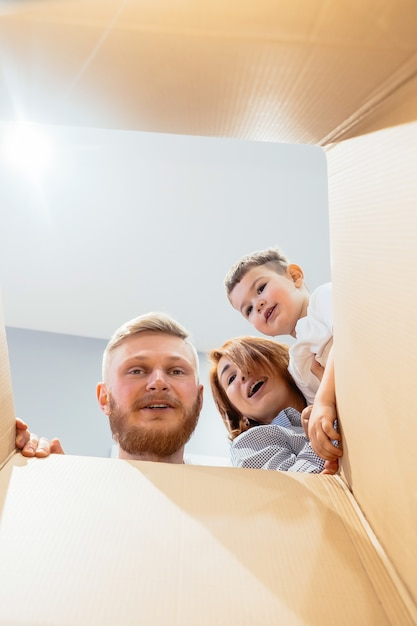Happy family just moved in new house and looking at box Free Photo