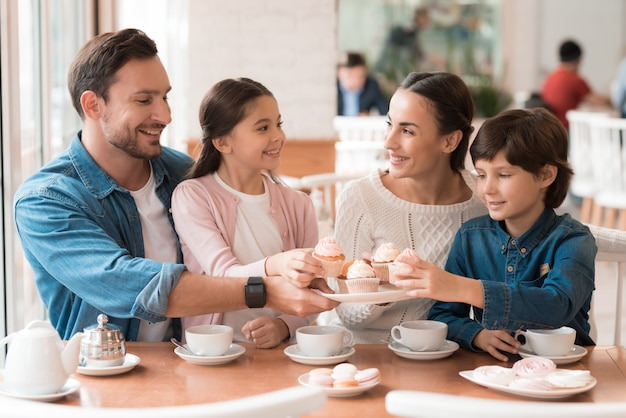 Happy family kids taking cupcakes from plate. Premium Photo