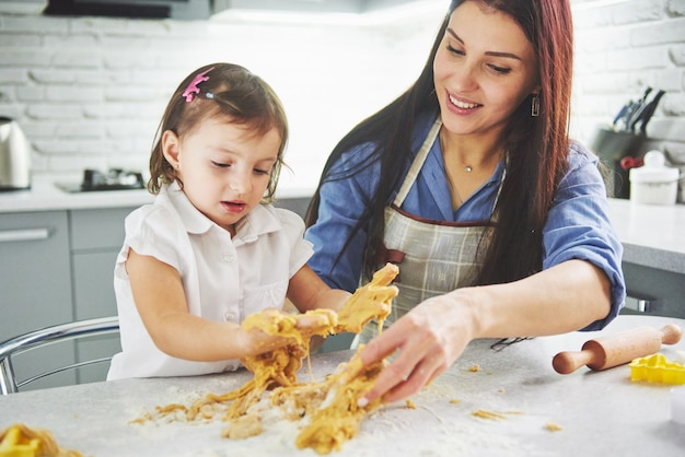 Happy family in the kitchen. mother and daughter preparing the dough, bake cookies. Free Photo