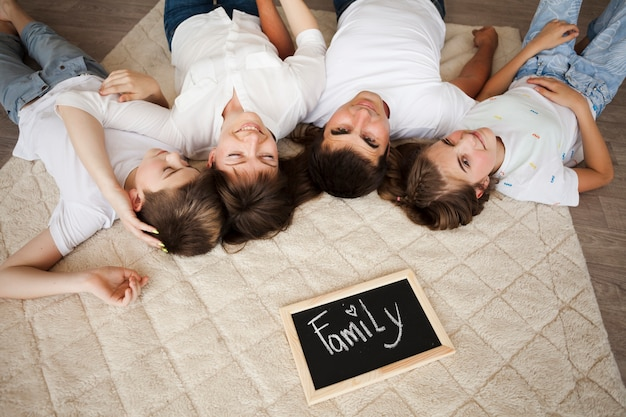 Happy family lying on carpet near slate with family text at home Free Photo