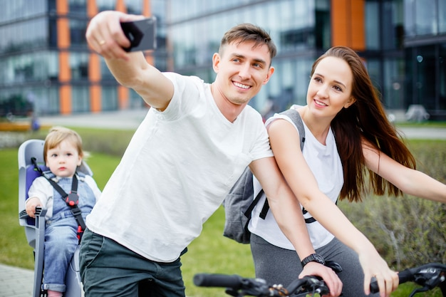 A happy family makes selfie on a smartphone while walking on bicycles Premium Photo