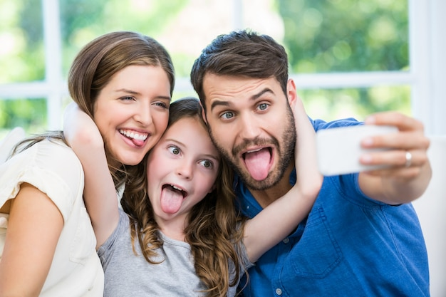 Happy family making faces while clicking selfie Premium Photo