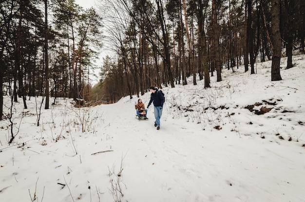 Счастливая семья: мужчина несет деревянные сани с девушкой на санях, гуляя в лесу на открытом воздухе. прогулка на праздничных выходных в зимнем парке. Premium Фотографии