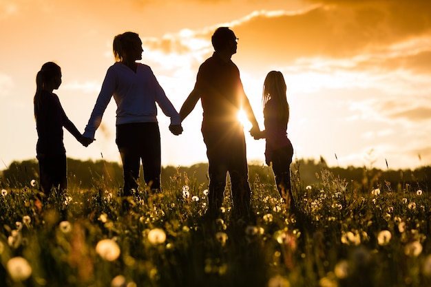 Happy family on meadow at sunset Premium Photo