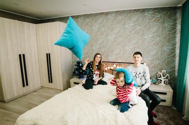 Счастливая семья: мама, папа и маленький сын в свитерах санта-клауса, играют и бросают подушки на кровать дома. каникулы. веселого рождества и счастливого нового года. Premium Фотографии