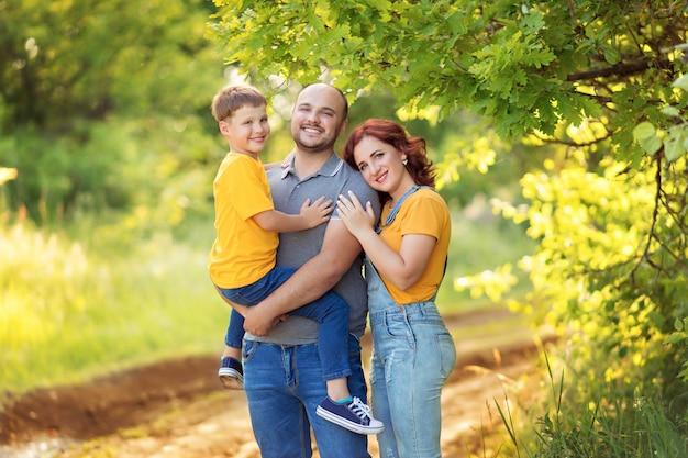 Счастливая семья, мама, папа, сын гуляют, обнимаются летом на свежем воздухе. Premium Фотографии
