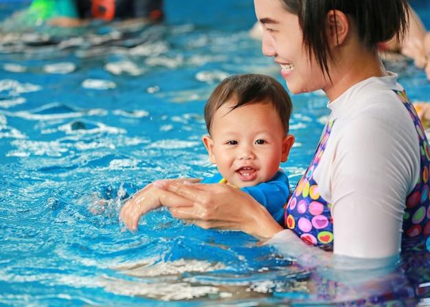 Happy family of mom teaching baby boy in swimming pool Premium Photo